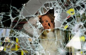 woman on phone staring out smashed window