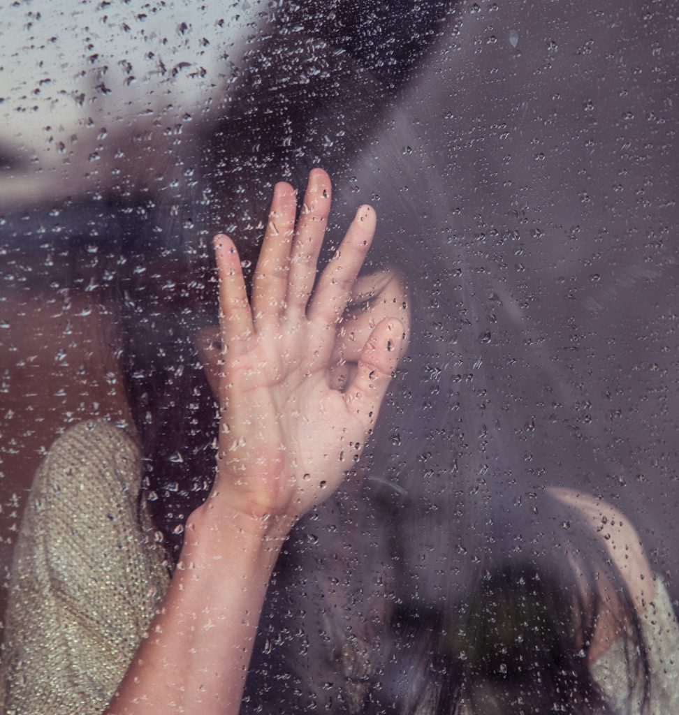 girl putting her hand towards a glass window